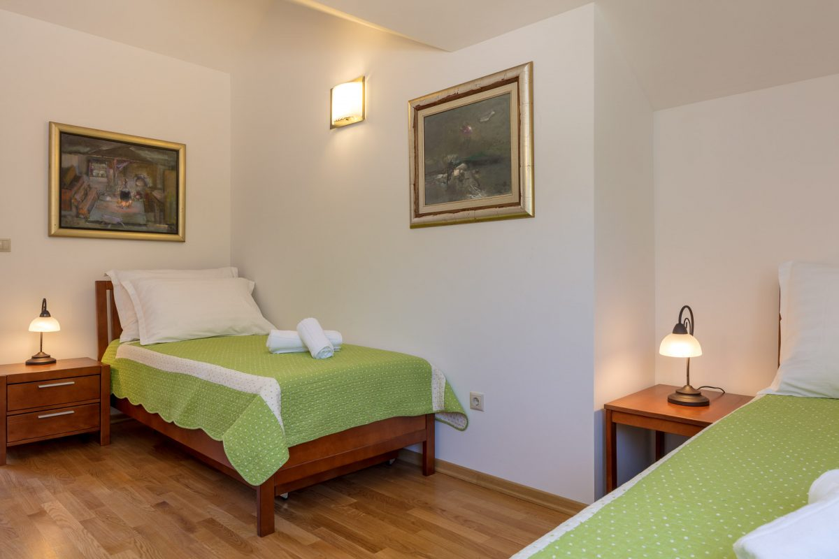 Twin bedded room in the Villa Roglic with art paintings on the wall