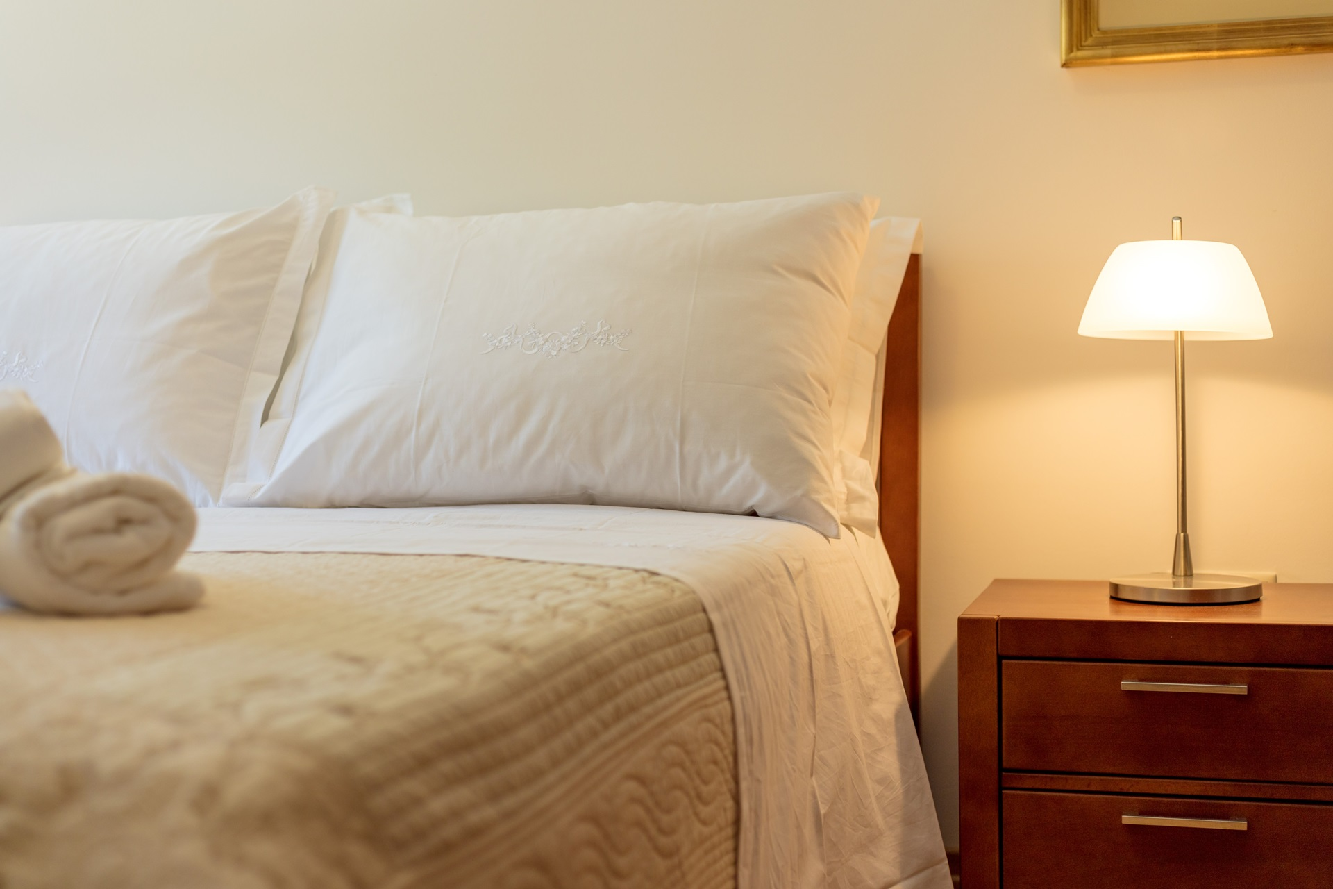 Soft pillow on a comfortable bed in the bedroom of the Villa Roglic and nightstand with the lamp