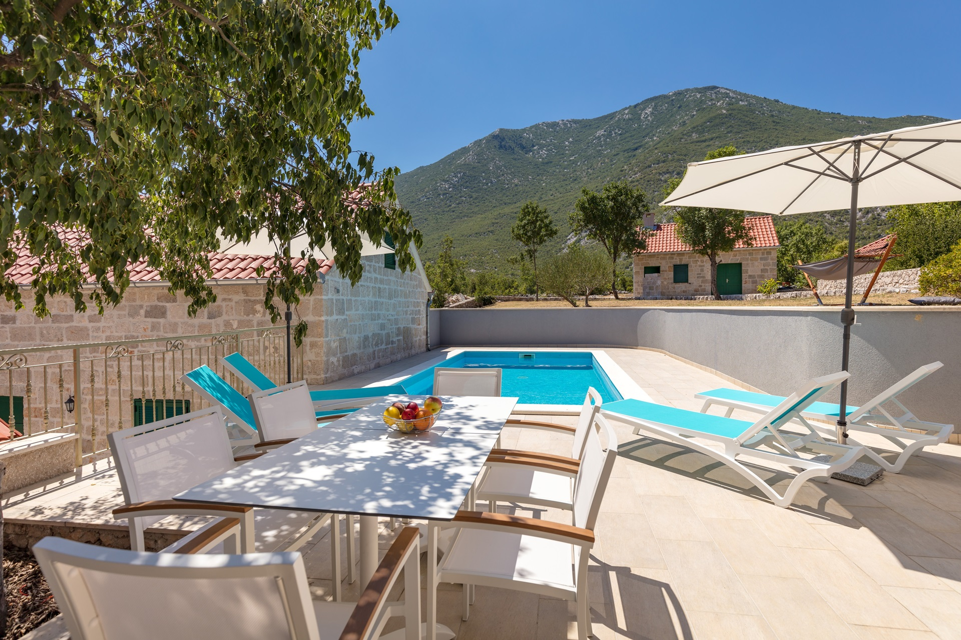 Outdoor dining area overlooking on the swimming pool and sunbeds with the parasols